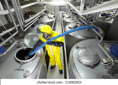 fully protected in yellow uniform,mask,and gloves technician filling large  silver tank in factory