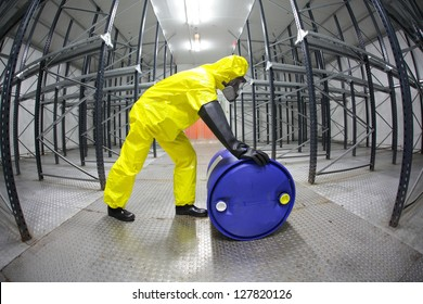 fully protected in yellow uniform,mask,and rubber gloves technician,rolling the barrel with toxic substance in empty warehouse - fish eye lens