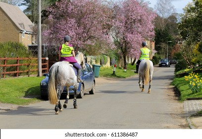 Fulwell Road, Finmere, Oxfordshire, United Kingdom, March 26, 2017: Female riders and horses on village road wearing Please Pass Wide & Slow sign on fluorescent jacket Oxfordshire UK