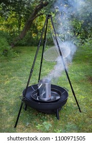 fuming barbecue charcoal chimney starter on a black tripod swivel grill in the garden