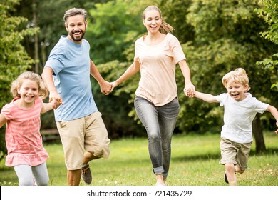 Fun and active family running together with joy in the nature