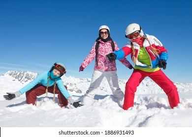 Animation amusante dans la neige pour trois filles en vacances d'hiver dans les Alpes de Haute Savoie, jouant dans la neige sur les pistes de ski.
