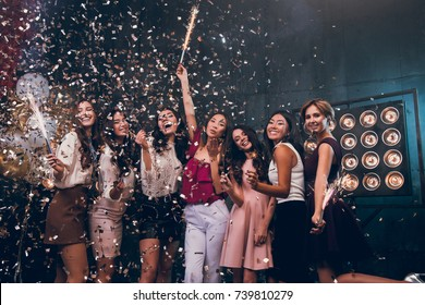 Fun is all we need! Group of beautiful young people dancing together and looking happy. Company of a beautiful dress dancing and smiling with a sparkle and gold confetti. Happy Hew 2018 year!