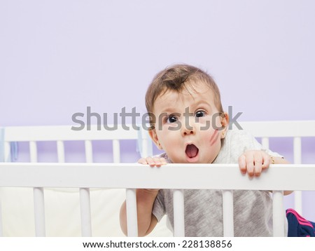 Fun baby with kiss mark on cradle in home bedroom.