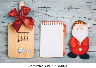 Fun background for the Christmas menu or recipes. Blank notebook, cutting board with utensils and miniature dishes and Santa Claus doll.