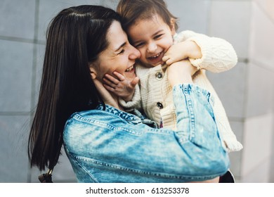 Fun beautiful woman and toddler girl play together and walking along city street. Good relationship of parent and child. Happy family moments of mom and toddler. Childhood and motherhood care.