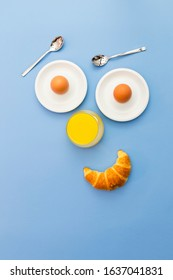 Fun breakfast concept with abstract happy smiling human face made of breakfast items on blue background