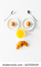 Fun breakfast concept with abstract sad human face made of breakfast items on white background