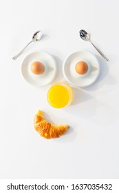Fun breakfast concept with abstract smiling happy human face made of breakfast items on white background