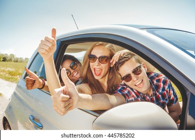 fun in car 3 cheerful friends in a automobile on summer trip waving hands through open window and leaving for vacation