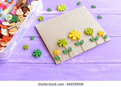 Fun card with flowers. Flowers buttons and leaves on blue wooden background. Plastic box with colorful buttons. Make kids crafts from recycled materials: cardboard and buttons
