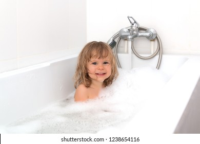 Fun cheerful happy toddler baby taking a bath playing with foam bubbles. Little child in a bathtub. Smiling kid in bathroom on white background. Infant washing and bathing. Hygiene and health care.