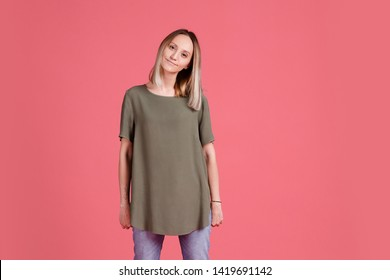 Fun and cheerful young blonde girl in a green oversized t-shirt and jeans posing on a pink background and looking at the camera. Pretty woman rejoices buying new appliances. Place for text