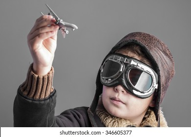 fun, child playing the aircraft pilot with hat and retro bomber jacket