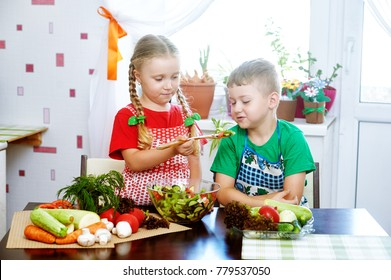 Fun children prepare salad vegetables . Happy kids in the kitchen . The concept of a healthy vegetarian diet