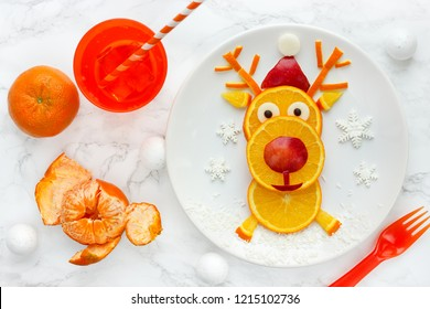 Fun Christmas food art idea - edible reindeer from orange slices on white plate, healthy fruit snack for kids