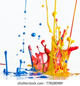 Fun conceptual colorful dancing thick paint splashes against a white background.