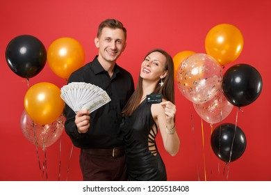 Fun couple celebrating birthday holiday party hold cash money, credit card isolated on bright red background air balloons St. Valentine International Women Day Happy New Year 2019 concept. Mock up