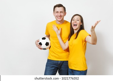 Fun crazy cheerful emotional young couple, woman, man, football fans in yellow uniform cheer up support team with soccer ball isolated on white background. Sport, family leisure, lifestyle concept
