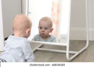 Fun cute baby seeing self in mirror