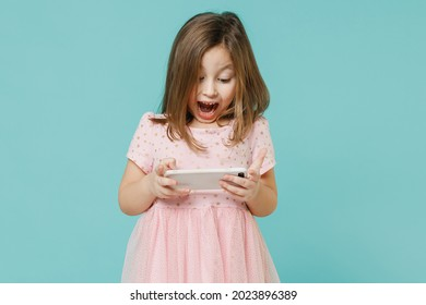 Fun cute kid girl 5-6 years old wears pink dress use play app on mobile cell phone hold gadget for pc video games isolated on pastel blue color background child studio Mother's Day love family concept