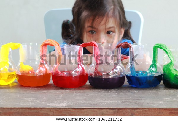 Fun and easy science.5 years old Asian girl making Walking Water experiment.Food color add to the water in the recycled bottle,water moving along the paper then color mixed.Concept of science for kid