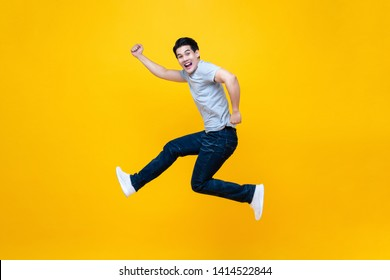 Fun energetic young handsome Asian man jumping in mid-air studio shot isolated on yellow background