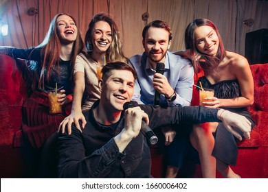 fun and entertainment concept. group of young people spend free time in karaoke, sing and have fun together, with friends