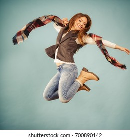 Fun and fashion concept. Woman fashionable casual style autumn girl jumping, flying in air on blue