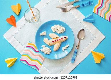Fun food idea for kids. children's Breakfast: plane made of banana and clouds made of curd on a blue plate. dreams of flying. creative lunch of the future pilot.