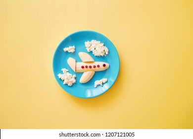 Fun food idea for kids. children's Breakfast: plane made of banana and clouds made of curd on a blue plate on yellow background. copy space