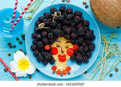 Fun food idea for kids - edible hawaiian girl face from pancake and blackberry, food art