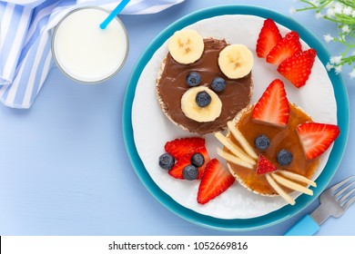 Fun food for kids - cute animal faces on crackers with chocolate and caramel spread decorated with fresh fruits - bananas, strawberries and blueberries for breakfast