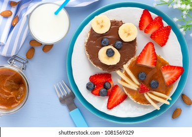 Fun food for kids - cute animal faces on toasts with chocolate and caramel spread decorated with fresh fruits - bananas, strawberries and blueberries for healthy breakfast
