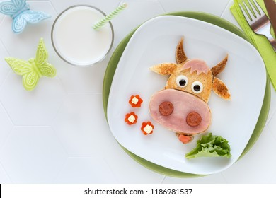 Fun food for kids - cute cow shaped sandwich with ham sausages served with a glass of milk for breakfast or dinner