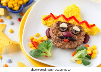 Fun food for kids - cute face of a mexican man with sombrero hat made of a meat burger or pattie and yellow rice, decorated with red beans, bell peppers and olives for Cinco de Mayo party