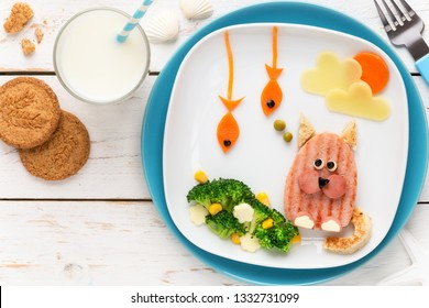 Fun Food for Kids - cute funny cat made of grilled meat ham burger with fish shaped carrots and broccoli, sweet corn and cheese