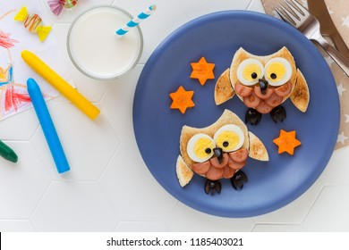 Fun food for kids - cute little owls shaped sandwiches or toasts with sausages and eggs. Overhead view