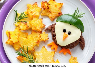 Fun Food for Kids - cute little penguin shaped beef hamburget in a hat with star shaped roast potatoes with aromatic fresh rosemary