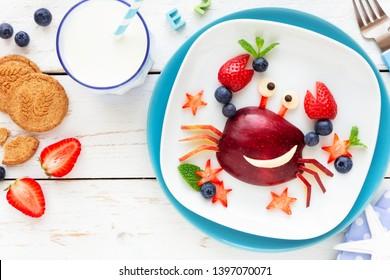 Spaß Essen für Kinder. Lächelnde, feine Krabbe aus frischen Früchten - Apfel, Erdbeeren, Heidelbeeren und frische Minze - für ein gesundes Frühstück mit Milch und Keksen
