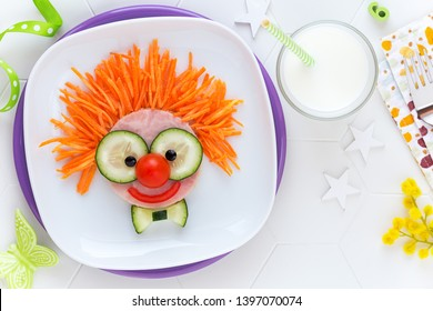 Vergnügen für Kinder - süßes, lächelndes Clown-Gesicht auf Schinken-Sandwich mit frischen Gurken, Karotten und Tomaten für ein gesundes Mittagessen für Kinder. Kreative Kochidee