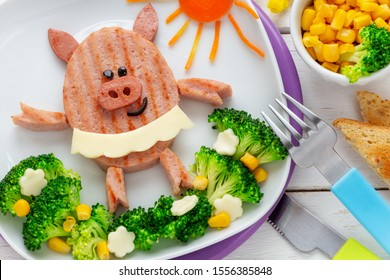 Fun Food for Kids - cute smiling ballerina pig made of a ham hamburger garnished with with broccoli florets,  sweet corn and cheese flowers. Healthy dinner for children concept