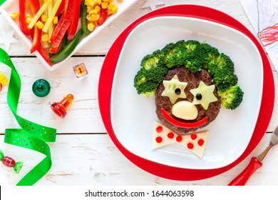 Fun food for kids - cute smiling face of a funny clown made of meat burger, broccoli and cheese. Healthy eating for children