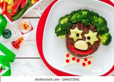 Spaß Essen für Kinder - süßes Lächeln eines lustigen Clowns aus Fleischburger, Broccoli und Käse. Gesunde Ernährung für Kinder