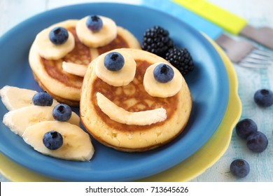 Fun food for kids - cute smiling faces on sweet pancakes for breakfast with bananas, fresh blueberries and blackberries. Creative cooking for children