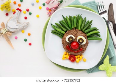 Fun food for kids - cute smiling clown face on a meat hamburger or ground meat pattie with green beans for a healthy dinner for children. Creative cooking idea