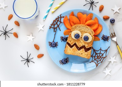 Fun food for kids - cute sweet chocolate spread sandwich monster decorated with fresh banana, blueberry spiders and apricots for breakfast