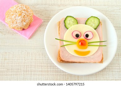 Fun food for kids - face on bread, made from cheese, ham, tomato, cucumber and pepper.