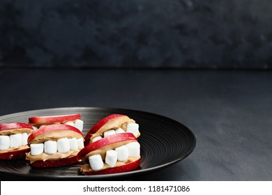 Fun food for kids. Halloween apple mouths filled with peanut butter with mini marshmallows for teeth. Shallow depth of field with selective focus on lips in the center of plate.  Free space for text.