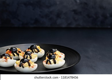 Fun food for kids. Halloween boiled eggs with black olive spiders on top of them. Alternative to candy.
